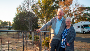An older couple standing by a fence with a caravan in the background